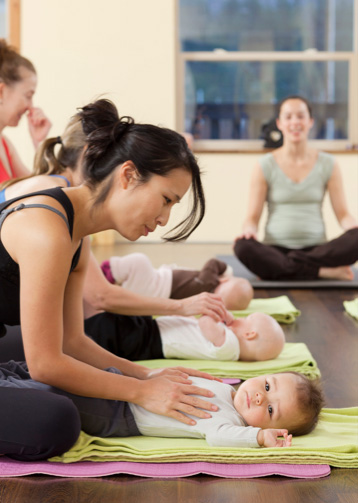 Mothers and children practising baby yoga